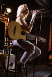 Performer singing while holding guitar at nightclub. Female performer singing while holding guitar on stage at nightclub Royalty Free Stock Image
