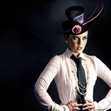 Performer In The Spotlight. An actress dressed in typical vaudeville costume with a fascinator hat and tie performing on a darkened stage facing out of frame to Royalty Free Stock Photo