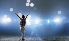 Performer on stage. Back view of girl with hands up standing in stage lights stock image