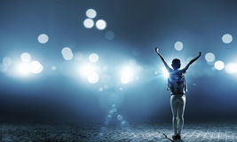 Performer on stage. Back view of girl with hands up standing in stage lights stock images