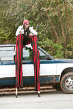 Performer On Stilts Sits On Top Of Car Stock Image