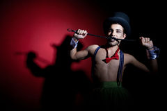Performer in top hat with whip. Performer in top hat biting leather whip Stock Photos