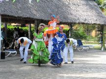 Performers in traditional dress dance at resort in Cuba. A festive dance troupe perform in traditional dress for Cuban Day at tourist resort royalty free stock photography