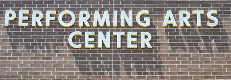Performing Arts Center. Simple white block letters fastened to a brick wall of a performing arts center were dreams can come true and performances that will royalty free stock photography