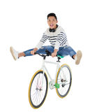 Performing difficult stunt. Excited Vietnamese young man performing stunt on bicycle Stock Photography