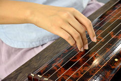 Performing of seven-stringed plucked instrument. Female hand in performing of seven-stringed plucked instrument, shown as famous Chinese traditional art, and Royalty Free Stock Photos