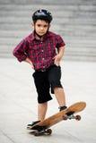 Performing stunt. Little boy in helmet performing stunt on skateboard Royalty Free Stock Image