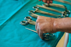 Performing surgery. Surgical instruments and tools including scalpels, forceps and tweezers arranged on a table for a surgery Royalty Free Stock Images