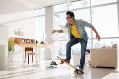Performing a trick. Excited Vietnamese skateboarder performing a trick in his room Stock Photography