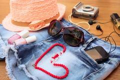 夏天妇女的辅助部件:红色太阳镜,小珠,牛仔布短缺,手机,耳机,太阳帽子,照相机,指甲油, perfum 免版税库存图片