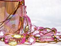 Perfum. The image of a bottle with perfumery water and the scattered thread of a beads Royalty Free Stock Image
