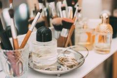 Perfumaria e cosméticos em uma tabela de molho com um espelho Foto de Stock Royalty Free