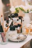 Perfumaria e cosméticos em uma tabela de molho com um espelho Fotografia de Stock Royalty Free