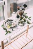 Perfumaria e cosméticos em uma tabela de molho na luz do dia Fotografia de Stock Royalty Free