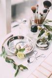 Perfumaria e cosméticos em uma tabela de molho na luz do dia Fotos de Stock