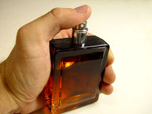Perfume. Bottle in the hand royalty free stock photo