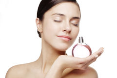 Perfume. Young female smelling a bottle of perfume Stock Photo