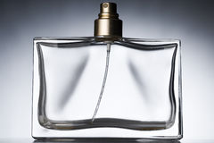 Perfume. An empty perfume bottle against grayish background Stock Photos