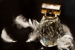 Perfume. Glass perfume bottle amongst white beaded feathers stock image