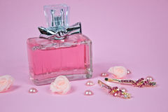 Perfume aromático cor-de-rosa com os gancho de cabelo dourados no rosa Foto de Stock Royalty Free