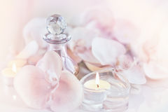 Perfume or aromatic oil bottle surrounded by flowers and candles Stock Photography