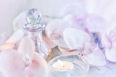 Perfume or aromatic oil bottle surrounded by flowers and candles Royalty Free Stock Photo