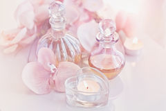 Perfume and aromatic oils bottles surrounded by flowers and cand Royalty Free Stock Photos