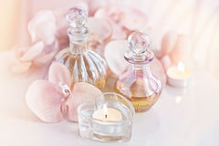 Perfume and aromatic oils bottles surrounded by flowers and cand Stock Images