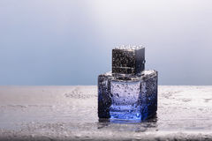 Perfume in blue bottle with water drops Royalty Free Stock Image