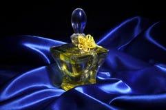 Perfume on blue satin. Perfume over of wavy blue satin Royalty Free Stock Photography