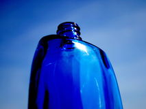 Perfume bottle. In the background of the sky, a bit artistical toned. Focus on the top stock image