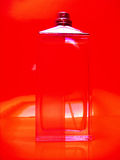 Perfume bottle. Cologne/perfume bottle against red background Royalty Free Stock Photos