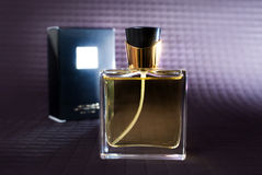 Perfume Bottle. A sleek gold and black perfume bottle and display box on a textured backdrop Royalty Free Stock Photography