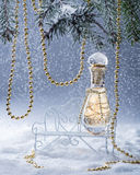 Perfume bottle on the bench in the snowy forest.Spruce branches is decorated of the gold beads. Royalty Free Stock Photos