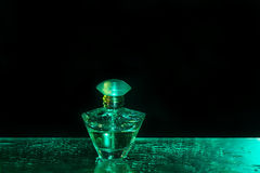 Perfume bottle on the black and green background. With watergrops royalty free stock photo