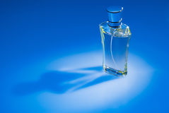 Perfume bottle on blue background Royalty Free Stock Image