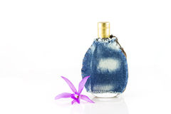 Perfume bottle in cloth bag adorned with orchid Stock Image