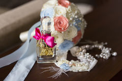 Perfume bottle with decorative crimson ribbon and wedding bouquet and garter for bride Stock Photos