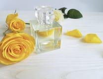 Perfume bottle female product yellow rose on a wooden. Perfume bottle yellow rose on a wooden composition product female Stock Image