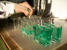 Perfume bottle filling. Operation with semi-automatic pump sistem and operator Stock Photo