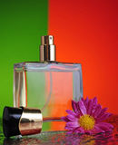 Perfume bottle with a flower. A bottle of perfume with a flower on a table with splashes. The background is half green and half orange Royalty Free Stock Photography