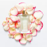 Perfume bottle with flower petals on light background. Perfumery, fragrance collection. Women accessories. Stock Image