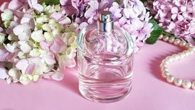 Perfume bottle with flowers and pearl necklace o Stock Images