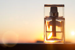 Perfume bottle on gold sunset background with copy space. Royalty Free Stock Images