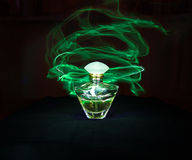 Perfume bottle and green light painting. On the black background royalty free stock photos