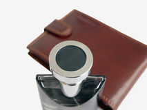 Perfume bottle leather case. Closeup of the top of a fancy perfume bottle with a leather case nearby.  White background Stock Photography