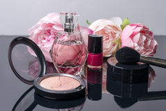 Perfume bottle, makeup brush, nail polish and blusher. Fashion woman still life. Pop female things on black background. With flowers. Beauty tools Royalty Free Stock Images