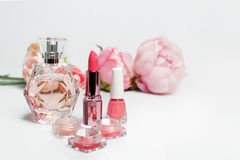 Perfume bottle, nail polish, lipstick. Fashion woman still life. Pop female things with flowers on white background. Perfume bottle, nail polish, lipstick Stock Photography