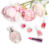 Perfume bottle, nail polish, lipstick. Fashion woman still life. Pop female things with flowers on white background. Perfume bottle, nail polish, lipstick Stock Photo