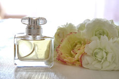 perfume bottle next to aromatic flowers on white table Royalty Free Stock Images